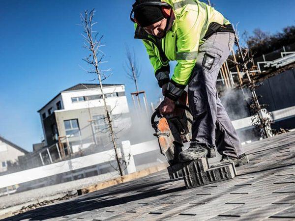 Bauarbeiter schneidet mit Fliesenschneider Pflasterstein