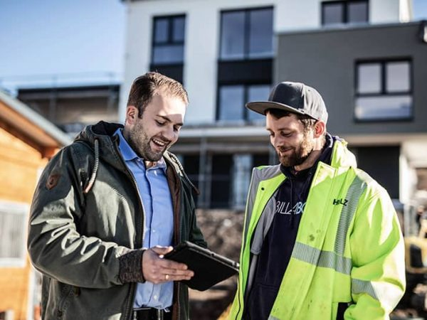 Baratungsgespräch zwischen Bauplaner und Bauerbeiter an privaten Grundstück