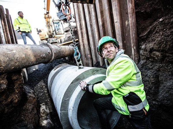Bauarbeiter hilft bei dem Ablassen des Kanalrohrs