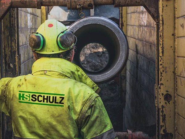 Kanalrohr wird in Schacht gelegt und Bauarbeiter kontrolliert