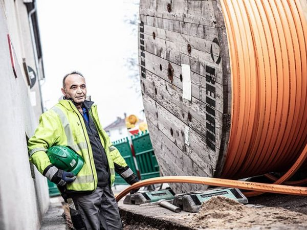 Bauarbeiter zieht an Kabeltrommel für die Verlegung von Leitungen