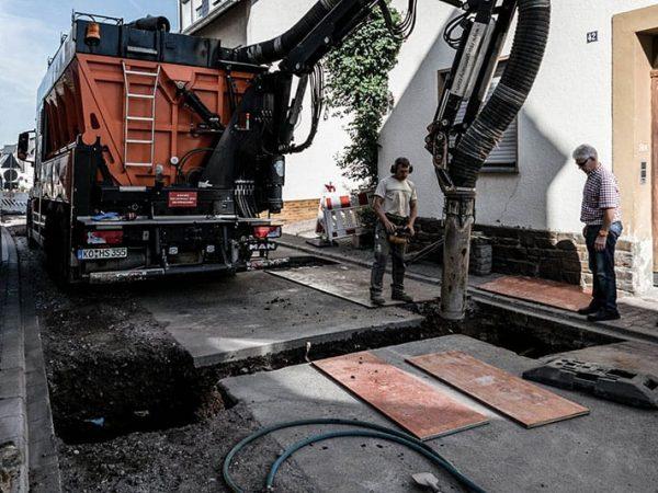 Saugbagger saugt Marteial unter der Straßendecke ab