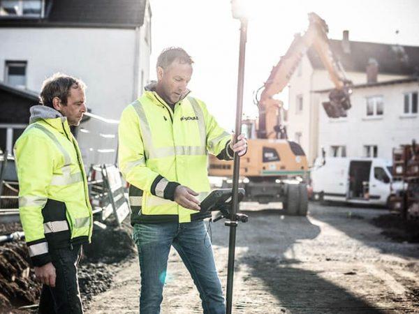 Zwei Bauarbeiter nehmen Bodenmessung vor